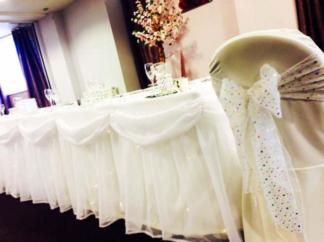 Twinkling fairylight top table swag with white chair cover and sparkly sash bow