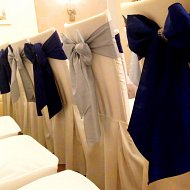 Navy and silver alternate taffeta sash bows with diamante decoration over ivory cotton chair covers