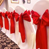 Romantic red satin sash bows over white cotton chair covers