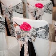 Beautiful black satin sash with white flock overlay bows over white cotton chair covers