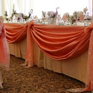 Draped pastel pink top table swagging with taffeta and white lace bow decoration