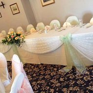 Delicate white lace top table drape with pastel green and white lace bow decorations
